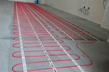Червоний кабельний мат розкладений на підлозі